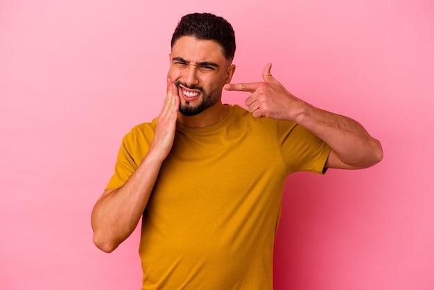 Homem jovem de raça mista, isolado em um fundo rosa, tendo uma forte dor nos dentes, dor molar.