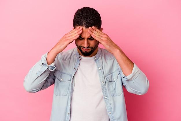 Homem jovem de raça mista isolado em um fundo rosa, tocando as têmporas e tendo dor de cabeça.