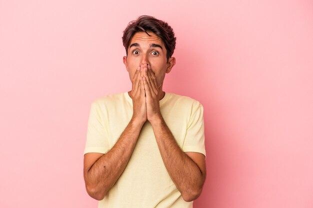 Homem jovem de raça mista isolado no fundo branco, cobrindo a boca com as mãos parecendo preocupado.