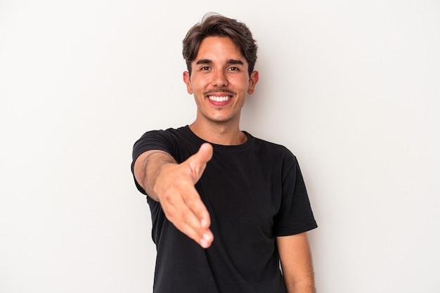 Homem jovem de raça mista isolado no fundo branco, esticando a mão na câmera em gesto de saudação.