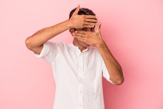 Homem jovem de raça mista isolado no fundo branco pisca para a câmera por entre os dedos, rosto coberto de vergonha.