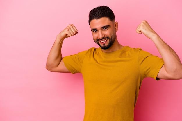 Homem jovem de raça mista isolado no fundo rosa, levantando o punho após uma vitória, o conceito de vencedor.
