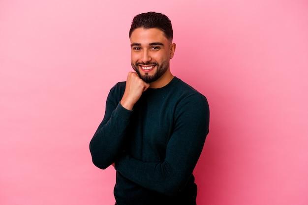 Homem jovem de raça mista isolado no fundo rosa, sorrindo feliz e confiante, tocando o queixo com a mão.