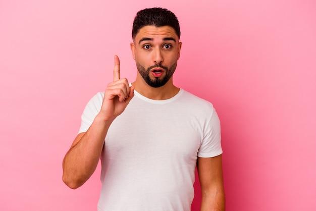 Homem jovem de raça mista isolado no fundo rosa, tendo uma ideia, o conceito de inspiração.