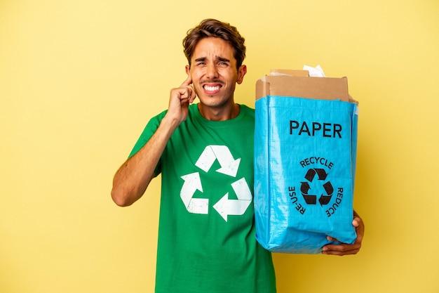 Homem jovem de raça mista, reciclando papel isolado em fundo amarelo, cobrindo as orelhas com as mãos.