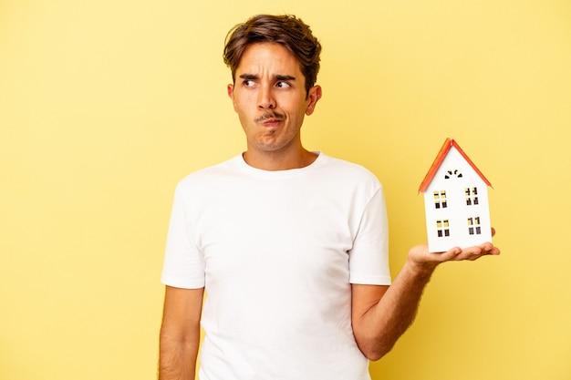 Homem jovem de raça mista segurando casa de brinquedo isolada em fundo amarelo confuso, sente-se duvidoso e inseguro.