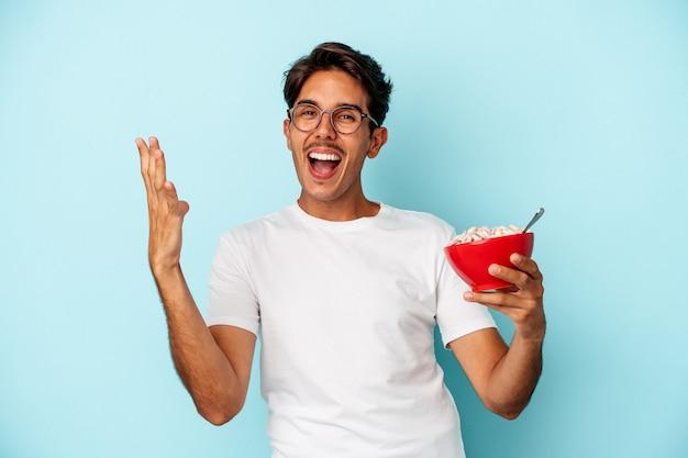 Homem jovem de raça mista segurando cereais isolados em fundo azul, recebendo uma agradável surpresa, animado e levantando as mãos.