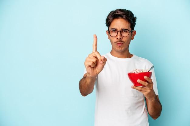 Homem jovem de raça mista segurando cereais isolados sobre fundo azul, mostrando o número um com o dedo.