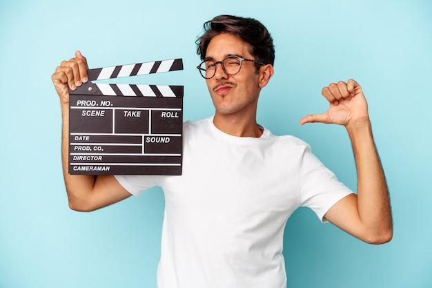 Homem jovem de raça mista segurando claquete isolada em fundo azul sente-se orgulhoso e autoconfiante, exemplo a seguir.