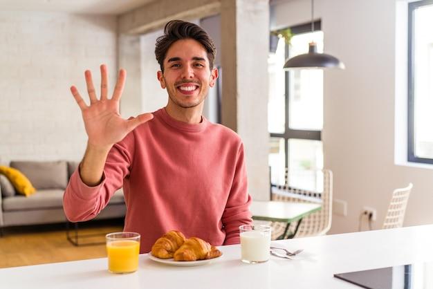 Homem jovem de raça mista tomando café da manhã em uma cozinha de manhã sorrindo alegre mostrando o número cinco com os dedos.