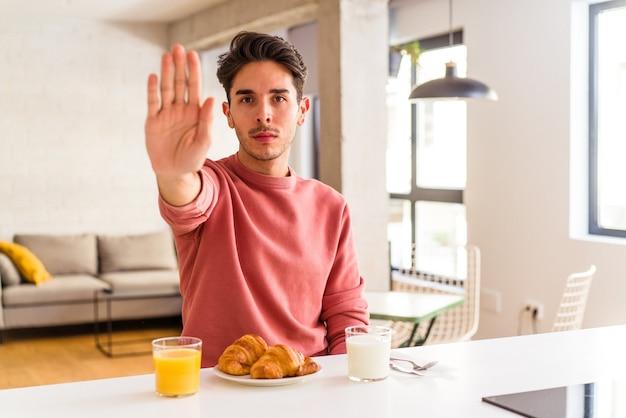 Homem jovem de raça mista tomando café da manhã em uma cozinha de pé com a mão estendida, mostrando o sinal de pare, impedindo-o.