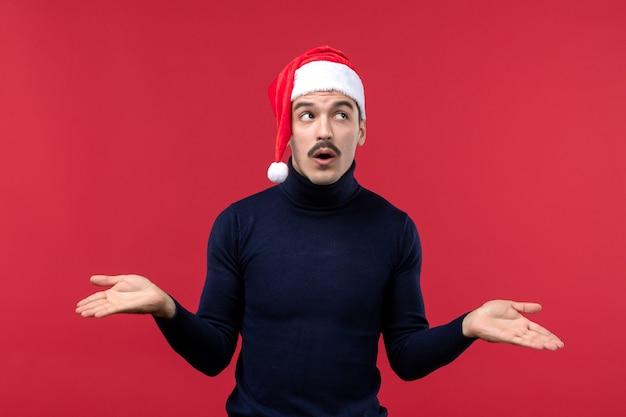 Homem jovem de vista frontal com expressão pensativa sobre fundo vermelho