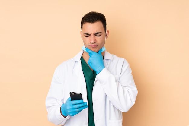Homem jovem dentista segurando ferramentas na parede bege pensando e enviando uma mensagem