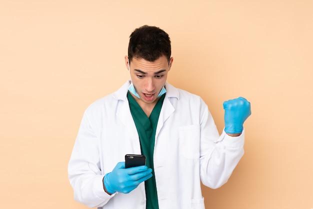Homem jovem dentista segurando ferramentas na parede bege surpreso e enviando uma mensagem