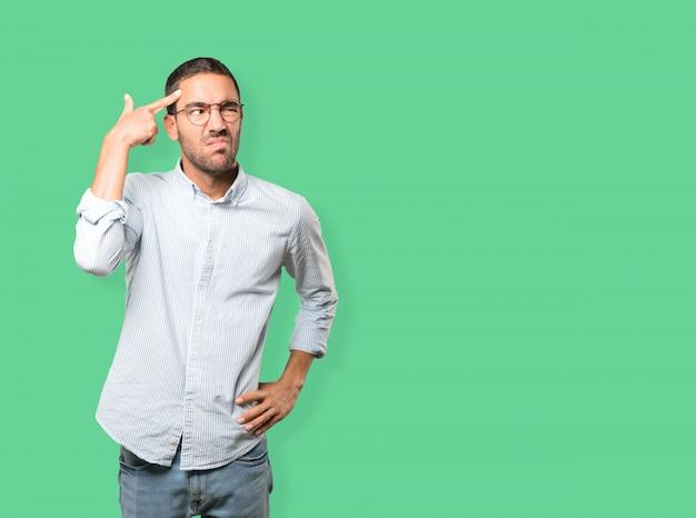 Homem jovem deprimido, fazendo um gesto de suicídio