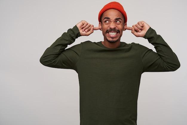 Homem jovem descontente, de pele escura, de olhos castanhos e barba que insere os indicadores nas orelhas enquanto fica em pé sobre o branco, evitando sons irritantes