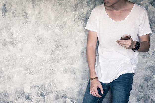 Homem jovem, desgastar, branca, t-shirt, e, calças brim azul, segurando, esperto, telefone, e, ficar