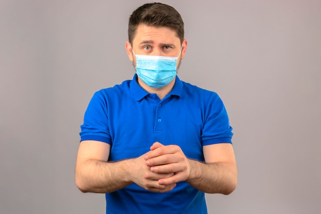 Homem jovem, desgastar, camisa polo azul, em, máscara médica protetora, com, expressão cética, segurar passa, junto, ficar, parede branca isolada