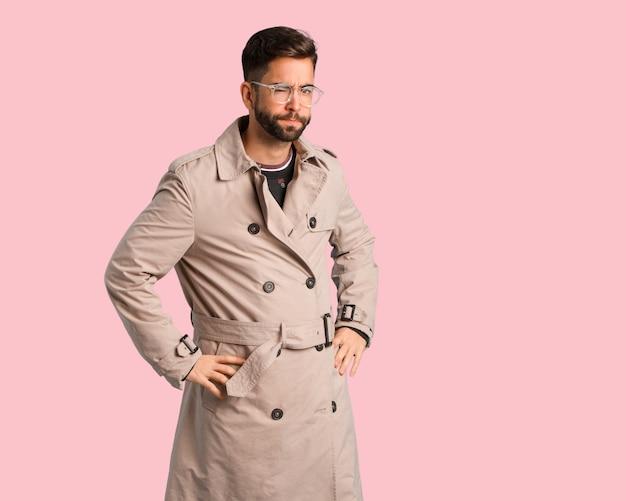 Homem jovem, desgastar, casaco trench, bronca, alguém, muito, zangado