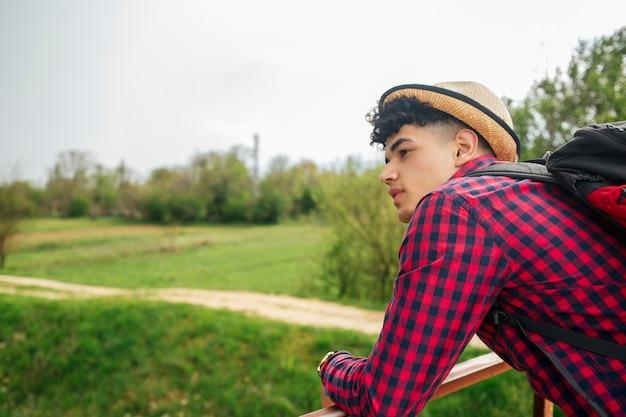 Homem jovem, desgastar, chapéu, carregar, mochila, olhando