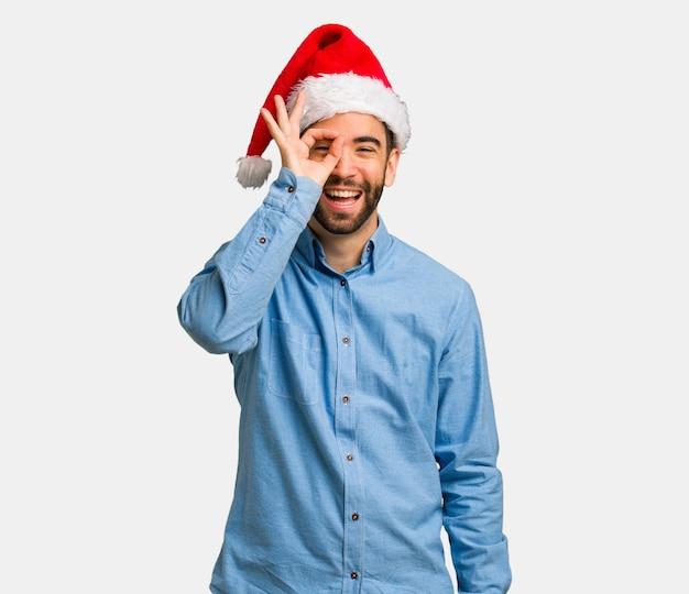 Homem jovem, desgastar, chapéu santa, confiante, fazendo, ok, gesto, ligado, olho