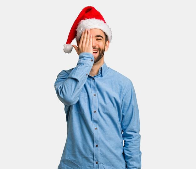 Homem jovem, desgastar, chapéu santa, shouting, feliz, e, cara covering, com, mão