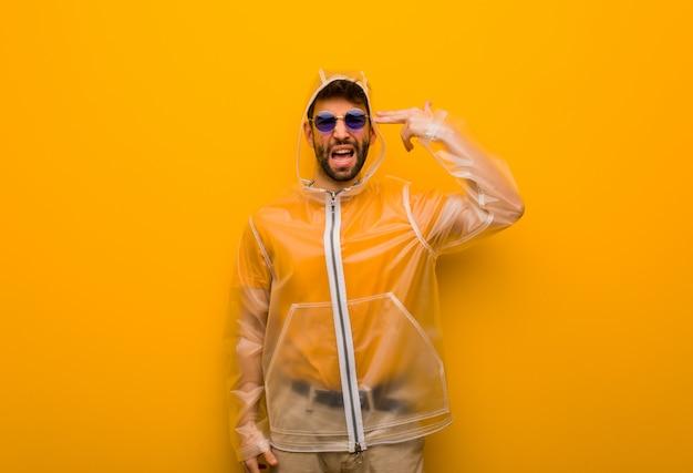 Homem jovem, desgastar, um, casaco chuva, fazendo, um, gesto suicídio
