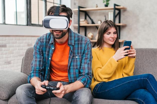 Homem jovem, desgastar, virtual, realidade, óculos, jogando videogame, com, dela, esposa, usando, telefone móvel
