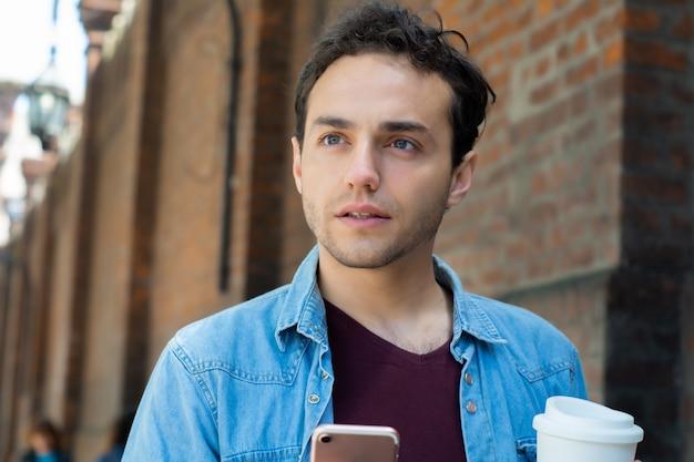 Homem jovem, digitando, mensagem, com, telefone móvel