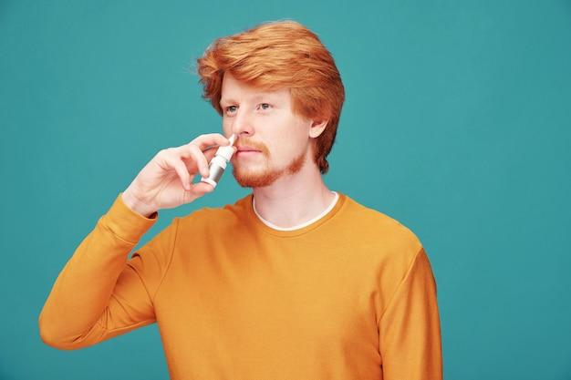 Homem jovem doente ou alérgico com corrimento nasal usando spray para curar alergia em flores sazonais, pele de animal ou comida sobre parede azul