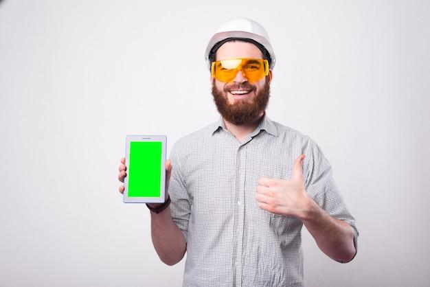 Homem jovem e alegre, engenheiro usando capacete, mostrando o polegar e segurando um tablet com tela verde