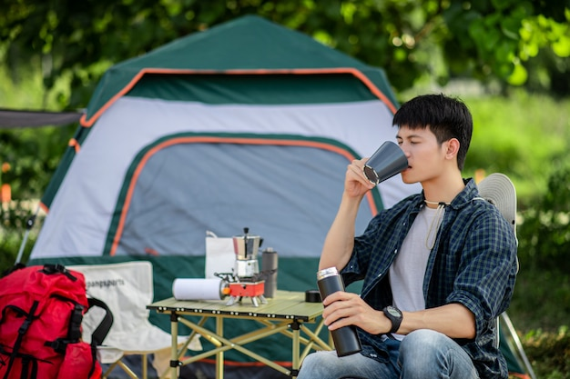 Homem jovem e alegre, mochileiro, sentado em frente a uma barraca na floresta com um conjunto de café e fazendo um moedor de café fresco durante o acampamento nas férias de verão