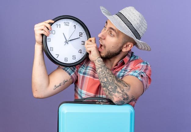 Homem jovem e ansioso viajante caucasiano com chapéu de palha de praia segurando e olhando para o relógio atrás da mala, isolado no fundo roxo com espaço de cópia