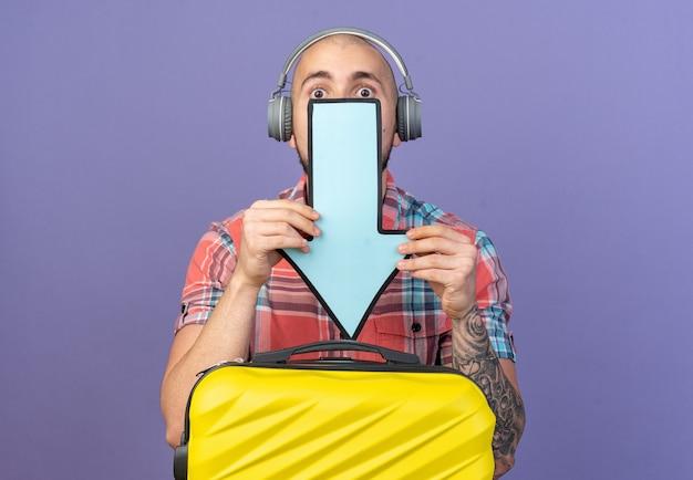 Homem jovem e ansioso viajante caucasiano com fones de ouvido segurando uma seta apontando para baixo, atrás de uma mala, isolada em um fundo roxo com espaço de cópia