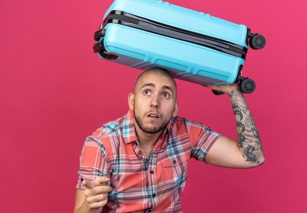 Homem jovem e ansioso viajante caucasiano segurando uma mala na cabeça e apontando para o lado isolado em um fundo rosa com espaço de cópia