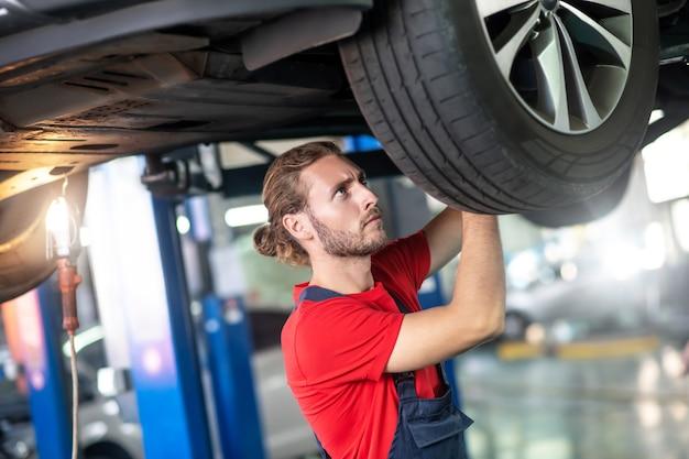 Homem jovem e atencioso experiente fazendo conserto de automóveis olhando para a roda de um posto de gasolina