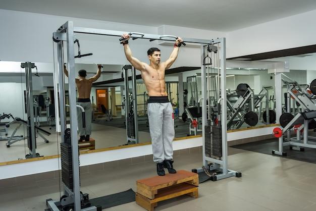 Homem jovem e atlético fazendo exercícios na barra transversal