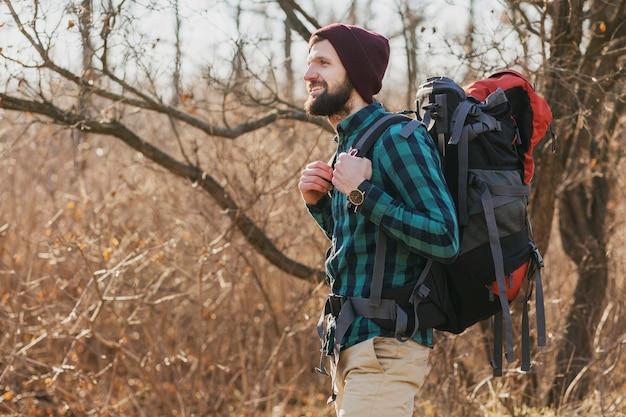 Homem jovem e atraente hippie viajando com mochila na floresta de outono usando camisa e chapéu xadrez