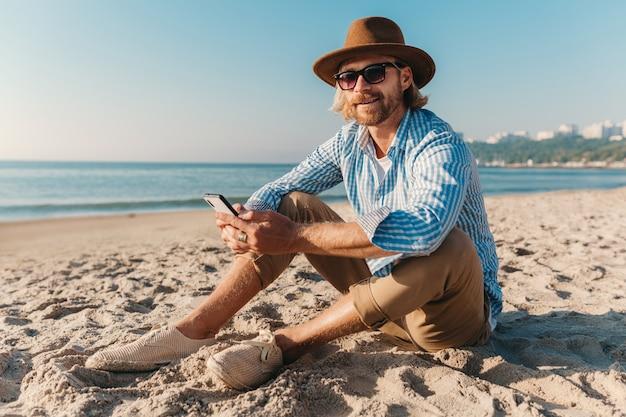 Homem jovem e atraente moderno sentado na praia à beira-mar nas férias de verão