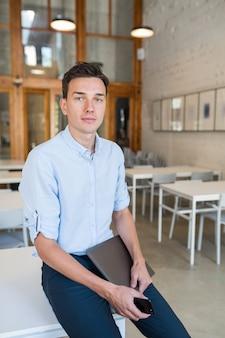 Homem jovem e atraente sorridente ocupado sentado em um escritório aberto, segurando um laptop