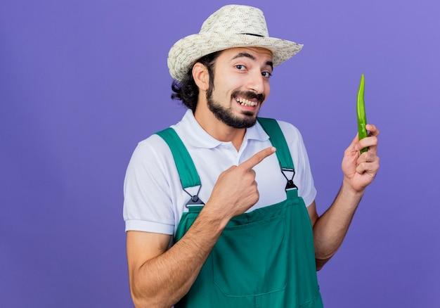 Homem jovem e barbudo jardineiro vestindo macacão e chapéu mostrando pimenta verde picante apontando com o dedo indicador para ela e sorrindo em pé sobre a parede azul