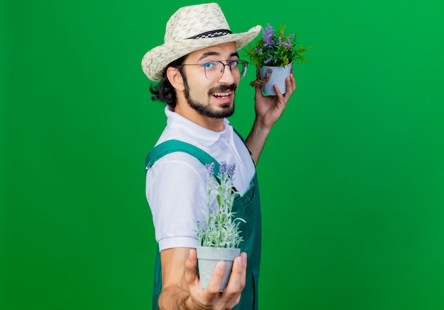 Homem jovem e barbudo jardineiro vestindo macacão e chapéu mostrando vasos de plantas felizes e sorrindo positivamente em pé sobre a parede verde