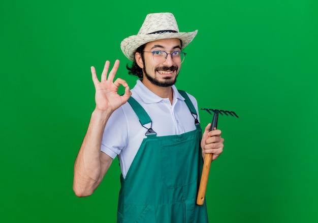 Homem jovem e barbudo jardineiro vestindo macacão e chapéu segurando um mini ancinho sorrindo mostrando sinal de ok