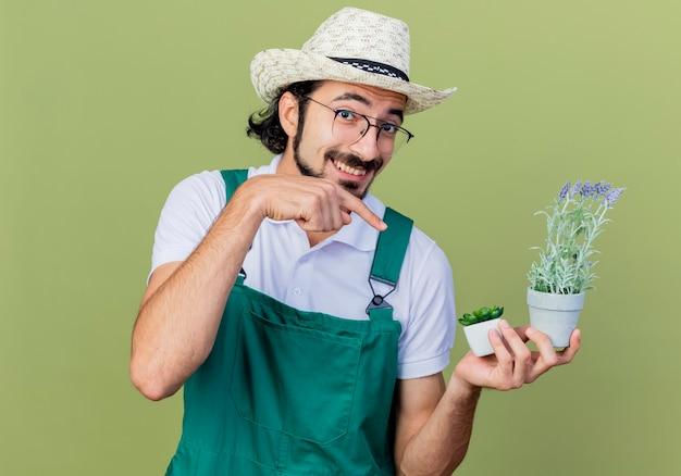 Homem jovem e barbudo jardineiro vestindo macacão e chapéu segurando uma planta em um vaso apontando com o dedo indicador para ela sorrindo alegremente em pé sobre a parede verde