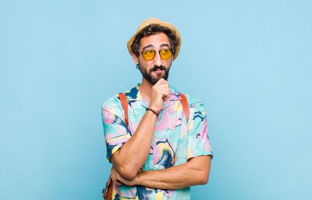 Homem jovem e barbudo turista se sentindo pensativo, imaginando ou imaginando ideias, sonhando acordado e olhando para cima para copiar o espaço