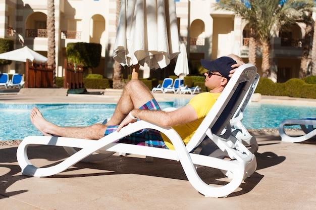 Homem jovem e bem sucedido, deitado numa espreguiçadeira no hotel perto da piscina