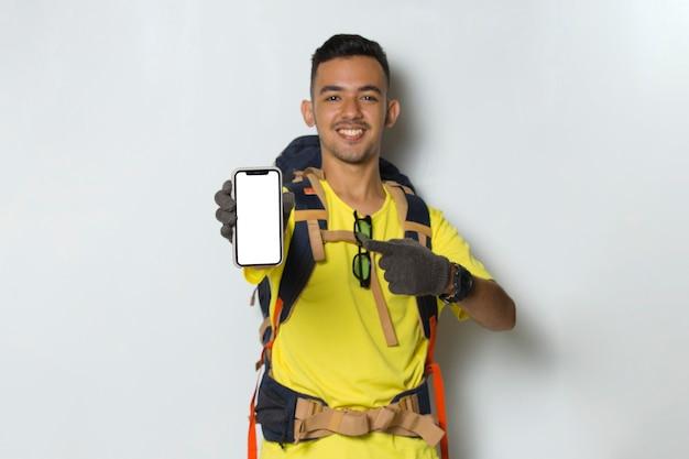 Homem jovem e bonito alpinista segurando um telefone celular com a tela em branco vazia isolada no fundo branco