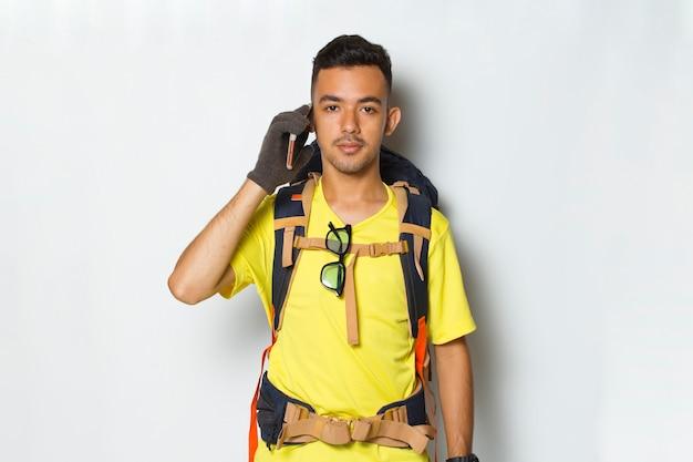 Homem jovem e bonito alpinista usando telefone celular isolado no fundo branco