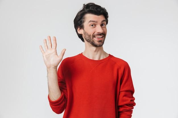 Homem jovem e bonito, barbudo, morena com suéter em pé sobre o branco, acenando