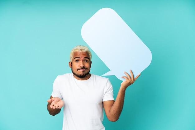 Homem jovem e bonito colombiano isolado em um fundo azul segurando um balão de fala vazio e tendo dúvidas